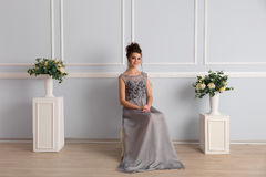 Gorgeous woman in transparent dress sits on chair Royalty Free Stock Images