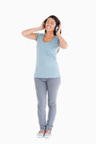 Gorgeous woman using her headphones while standing Royalty Free Stock Photos