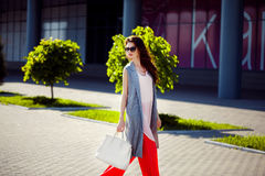 Gorgeous woman walking in mall. Horizontal outdoors shot of stylish young woman taking a walk to the mall Royalty Free Stock Images