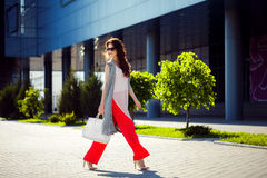 Gorgeous woman walking in mall. Horizontal outdoors shot of stylish young woman taking a walk to the mall Royalty Free Stock Photos