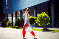 Gorgeous woman walking in mall. Horizontal outdoors shot of stylish young woman taking a walk to the mall Royalty Free Stock Image