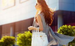 Gorgeous woman walking in mall. Horizontal outdoors shot of stylish young woman taking a walk to the mall Stock Photos