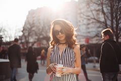 Gorgeous woman walking at street with cup of coffee.
