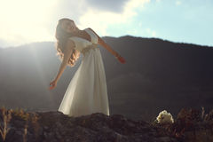 Gorgeous woman in white dress in evening light Stock Photo