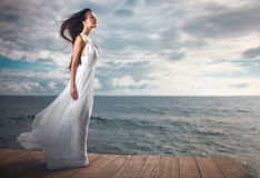 Gorgeous woman in white dress standing at pier close to cliffs. Royalty Free Stock Photography