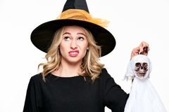 Gorgeous woman in witch costume holding Halloween skeleton decoration with disgust. Halloween concept. Gorgeous woman in witch costume holding Halloween stock photography