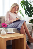 Gorgeous woman writing letter while sitting on sofa Royalty Free Stock Images