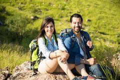 Portrait of a Hispanic couple trekking. Gorgeous women and her boyfriend sitting on a rock at the top of a mountain Stock Photography