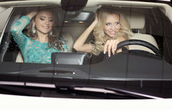 Gorgeous women with long hair wear luxurious dresses,posing in car Royalty Free Stock Images