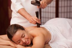 Young woman enjoying professional thai massage. Gorgeous women smiling with her eyes closed enjoying traditional thai hammer massage at spa center. Beautiful royalty free stock images