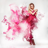 Gorgeous young adult blonde in pink dress with smo royalty free stock photography