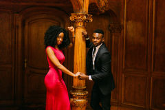 Gorgeous young african couple holding hands at the vintage column. Luxurious theatre interior background Stock Images