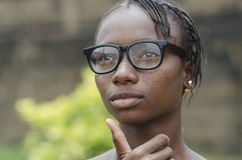 Gorgeous young african girl in eyeglasses thinking outdoors with blurred background. Young african girl in eyeglasses thinking outdoors with blurred background Stock Images