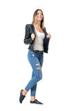 Gorgeous young beauty in ripped jeans and leather jacket looking up smiling Stock Photo