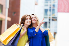 Gorgeous young blond with beautiful brunette pointing at a showcas Royalty Free Stock Image
