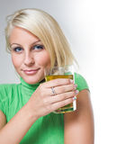 Gorgeous young blond with glass of juice. Royalty Free Stock Images
