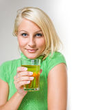 Gorgeous young blond with glass of juice. Royalty Free Stock Photography