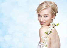 Gorgeous young blond woman with flower. Gorgeous young blond smilling woman with spring flower branch on bright blue background royalty free stock photos
