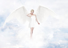 Gorgeous young blond woman as angel in heaven. With white wings stock photo