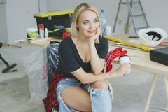 Trendy female sitting at carpenter workbench Royalty Free Stock Photography