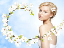Gorgeous young blond woman with spring flower branch. On bright blue background royalty free stock photo