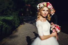 Gorgeous young blonde bride in elegant vintage white dress at su Stock Photo