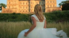 Gorgeous young blonde bride posing against to the old medieval castle in west Ukraine stock footage
