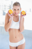 Gorgeous young blonde model holding two halves of an orange. Gorgeous young blonde model in white sportswear holding two halves of an orange stock photo