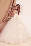Gorgeous young bride with blond curly hair, wears elegant wedding dress and crown Royalty Free Stock Photography