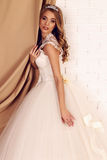 Gorgeous young bride with blond curly hair, wears elegant wedding dress and crown Royalty Free Stock Image