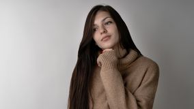 Gorgeous young brunette woman in warm knitted sweater on light grey background royalty free stock photography