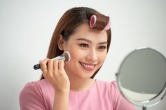 Gorgeous young brunette woman applying makeup stock image