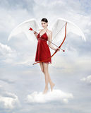 Cupid in clouds. Gorgeous young brunette woman as cupid angel in clouds with white wings, bow and arow Stock Photos