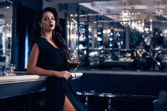 Gorgeous young brunette woman in dark dress with wine Stock Photos
