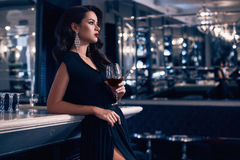Gorgeous young brunette woman in dark dress with wine stock images