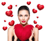 Gorgeous young brunette woman with heart shaped red pillow. Valentine' Day Royalty Free Stock Image