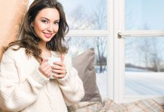 Hot beverage for cold days. Gorgeous young brunette woman holding cup of hot beverage royalty free stock photography