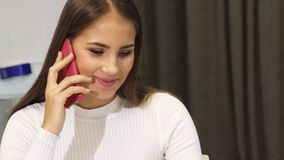 Gorgeous young business woman talking on the phone smiling joyfully. Stunning beautiful young business woman smiling cheerfully talking on the phone while stock video footage