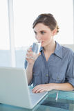 Gorgeous young businesswoman drinking a glass of water sitting at her desk Royalty Free Stock Image