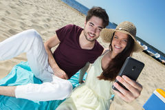 Gorgeous young couple sitting at beach and doing selfie Royalty Free Stock Images