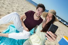Gorgeous young couple sitting at beach and doing selfie Stock Images