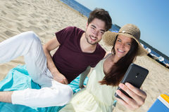 Gorgeous young couple sitting at beach and doing selfie Stock Image