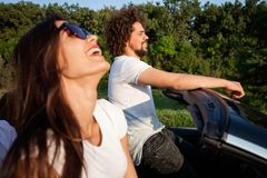 Gorgeous young dark-haired woman in sunglasses with curly young man are sitting and smiling in a black cabriolet on a stock images