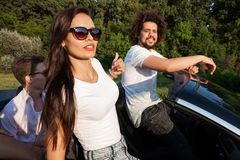 Gorgeous young dark-haired woman in sunglasses with young man are sitting in a black cabriolet on a sunny day. royalty free stock photography