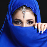 Gorgeous Young East Woman face portrait in hijab. Beauty Model Girl with bright eyebrows, perfect make-up, touching her Stock Images