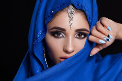 Gorgeous Young East Woman face portrait in hijab. Beauty Model Girl with bright eyebrows, perfect make-up, touching her Stock Photography