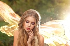 Gorgeous young enchantress with transparent wings and blond hair with beautiful appearance, model posing with closed royalty free stock photography