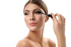 Gorgeous young female holding mascara brush isolated on white stock photography