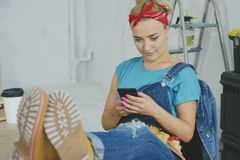 Smiling woman using smartphone sitting at workbench stock image
