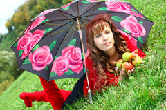 Gorgeous young girl. In red dress and boots lying with sappy apples under umbrella Royalty Free Stock Images